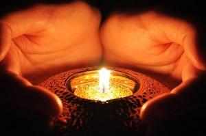 Hände um die Kerze
